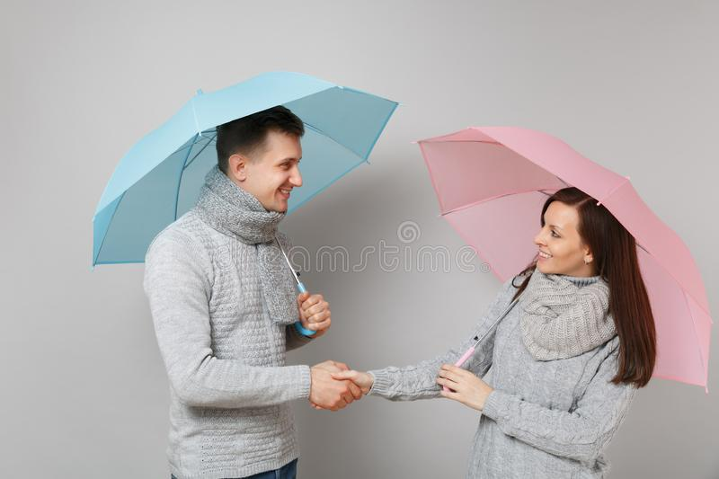 Couple girl guy in gray sweaters scarves together under umbrella isolated on grey wall background, studio portrait royalty free stock photo