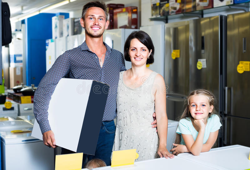 Couple with girl shopping electronics. Happy couple with girl buying new electronics and holding box in shop of household appliances royalty free stock photography