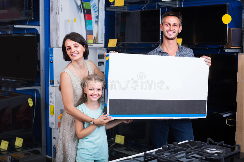 Couple with girl shopping electronics. Couple with girl shopping new electronics and holding box in shop of household appliances royalty free stock image