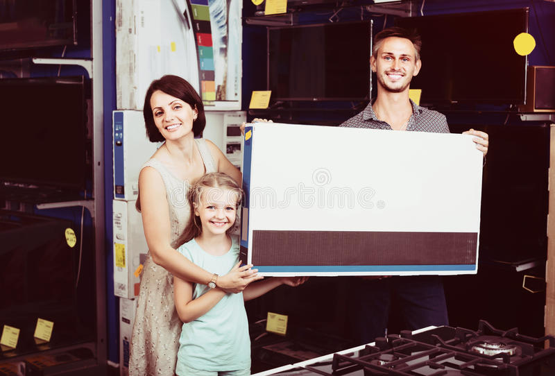 Couple with girl shopping electronics. Couple with girl shopping new electronics and holding box in shop of household appliances stock photography