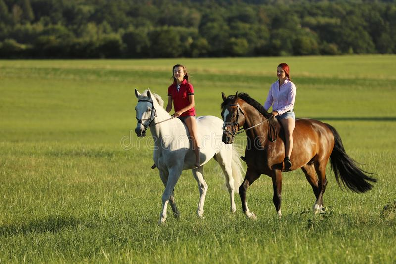 Two young girl riding horses on the walk without saddle in summer time royalty free stock images