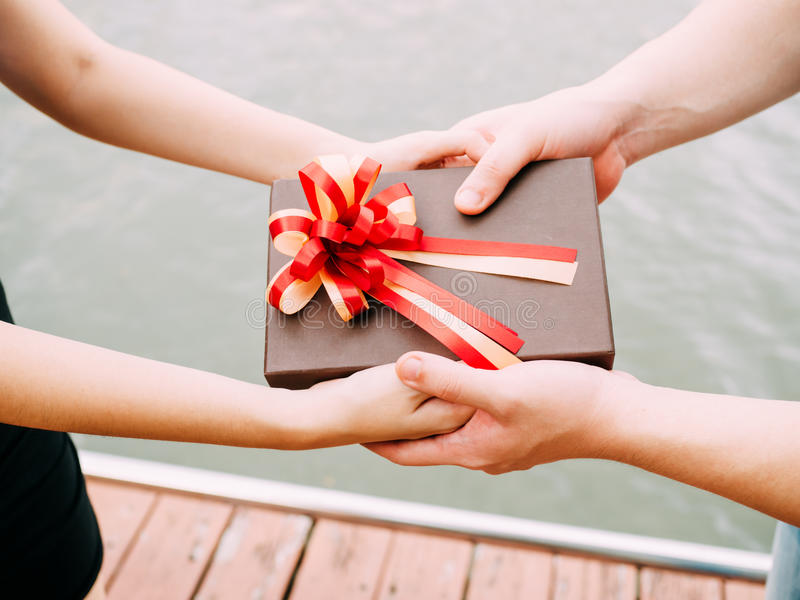 Couple giving a gift box to each other. Happy relationship in outdoor scene. Love and relationship concept.  stock image