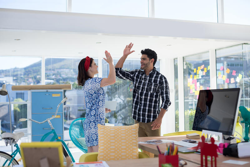 Couple giving high five to each other in the office royalty free stock photos