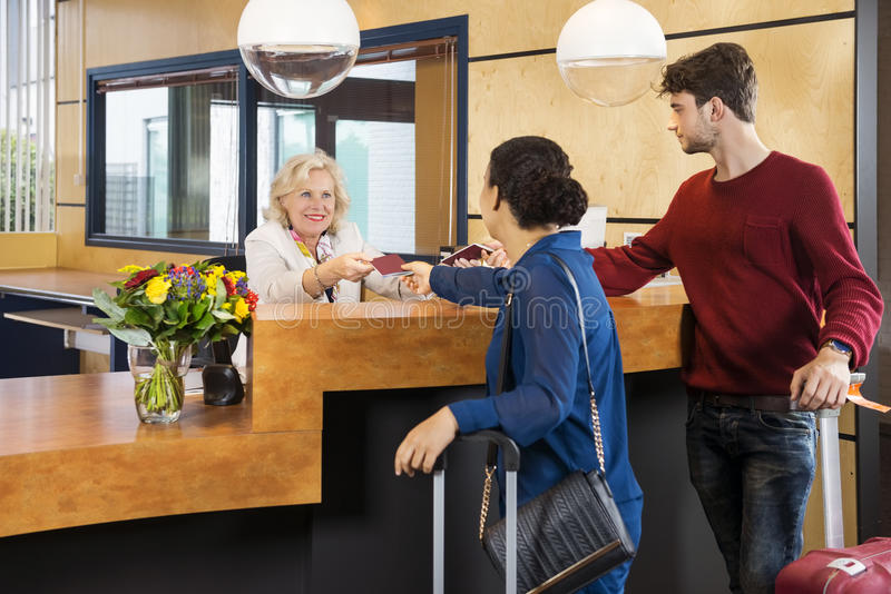 Couple Giving Passports To Receptionist. At counter in hotel royalty free stock images