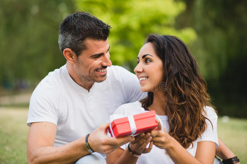 Couple giving present on birthday or anniversary celebration. Loving couple celebrating birthday or anniversary with a present royalty free stock photo