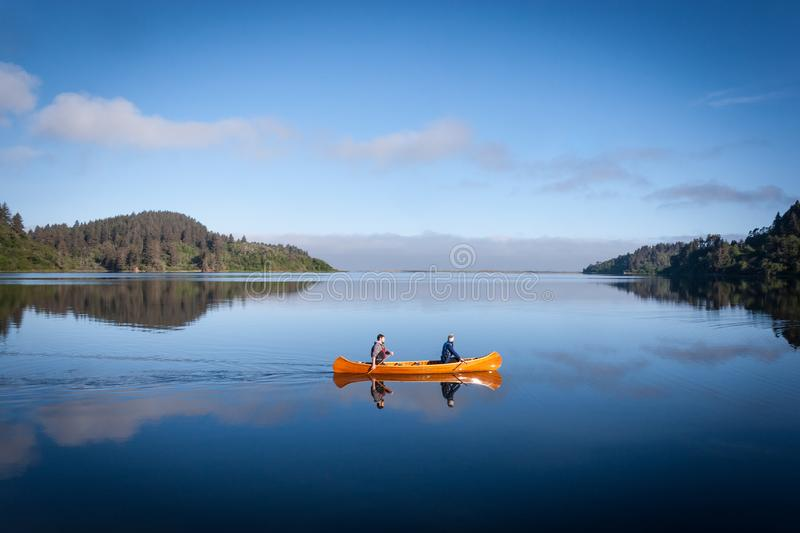 Early Morning Canoe Ride. A couple glides across a calm lagoon in the Humboldt National Lagoons State Park in California on an early morning, reflected in the royalty free stock image
