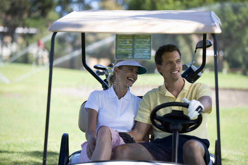 Couple in a golf buggy royalty free stock image