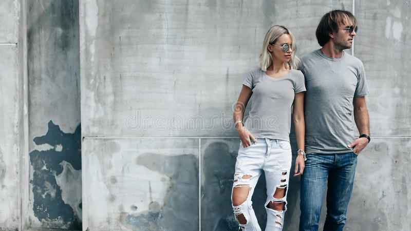 Couple in gray t-shirt over street wall stock photos