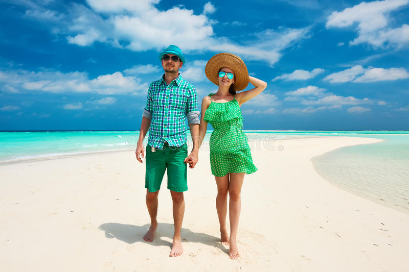 Couple in green on a beach at Maldives. Couple in green on a tropical beach at Maldives royalty free stock image