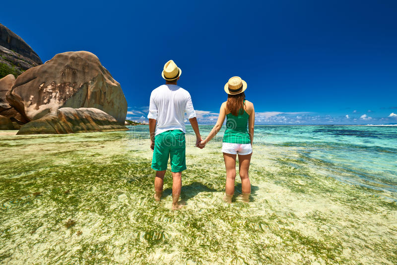 Couple in green on a beach at Seychelles. Couple in green on a tropical beach at Seychelles stock image