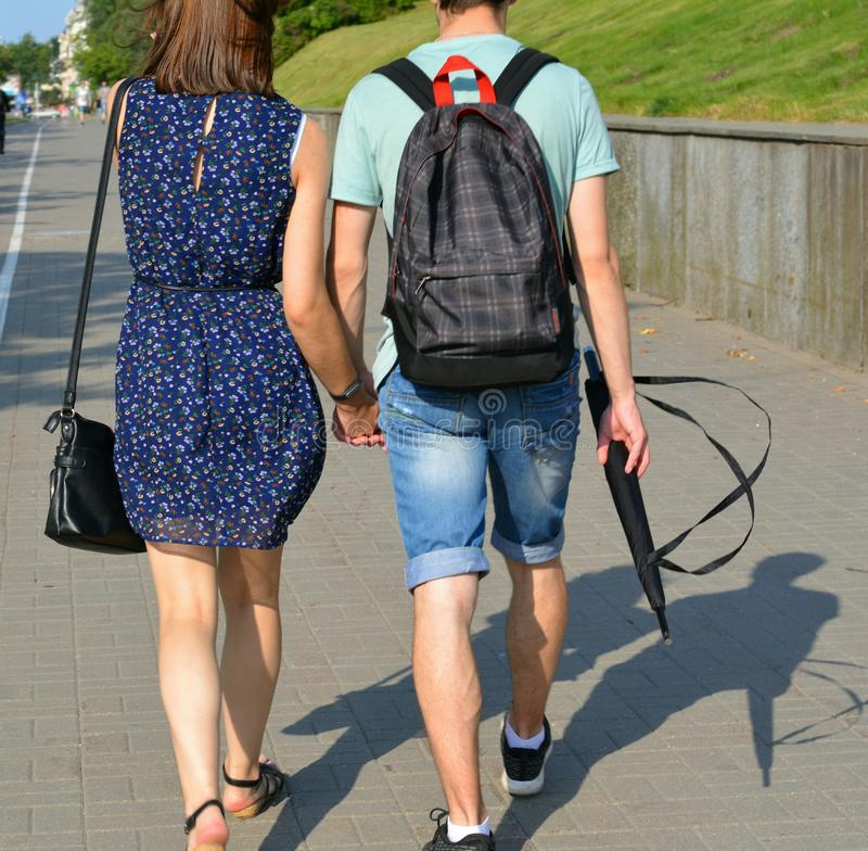Couple walk on a street road summer time in the Minsk city Belarus. Couple  green summer  nature two love pair active people trees branch grass    travel royalty free stock images