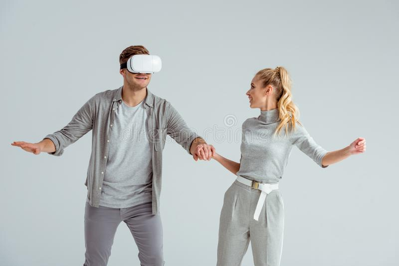Couple in grey clothing holding hands while man experiencing virtual reality isolated. On grey royalty free stock photos