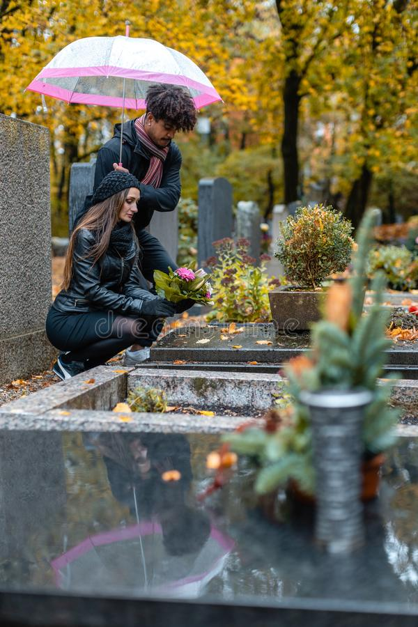 Couple in grief on a cemetery in fall stock photography