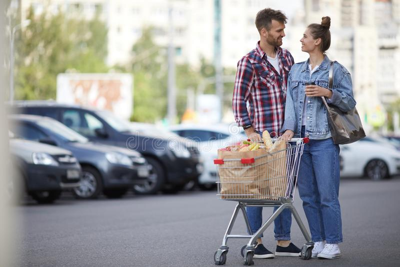 Couple with Groceries in Parking Lot stock photo