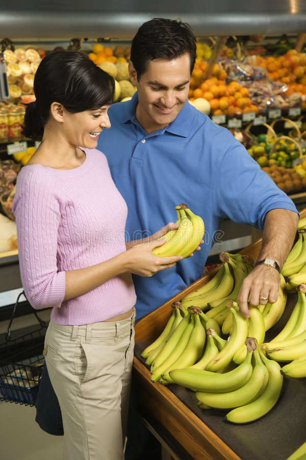 Couple grocery shopping. Caucasian mid-adult couple grocery shopping for bananas royalty free stock photo