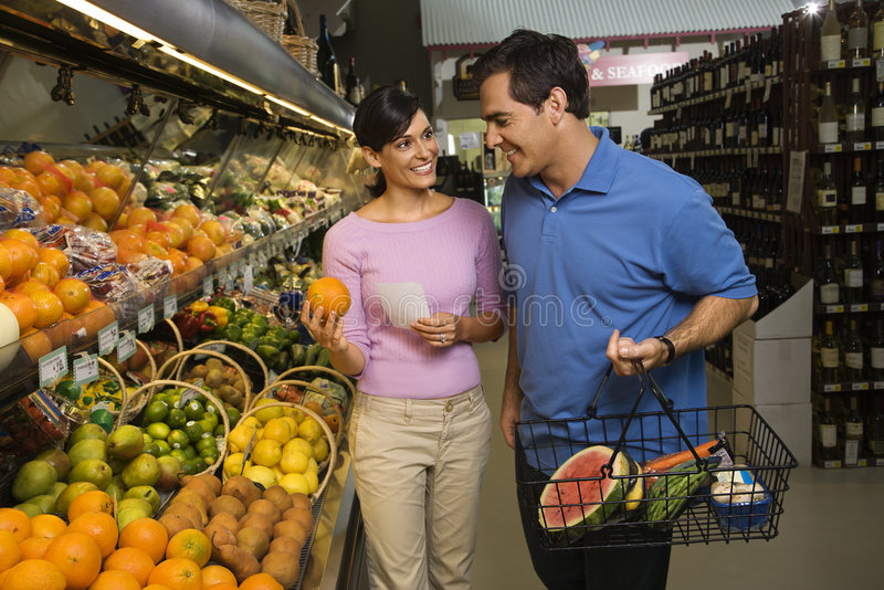 Couple grocery shopping. Caucasian mid-adult couple grocery shopping for fruit royalty free stock photography