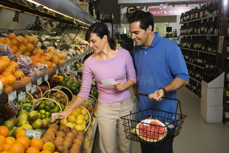 Couple grocery shopping. Caucasian mid-adult couple grocery shopping for fruit stock photos