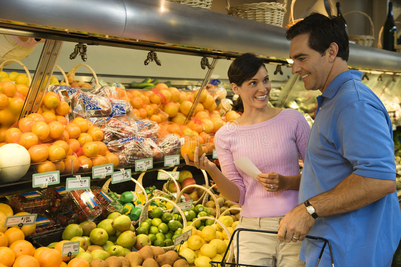 Couple grocery shopping. Caucasian mid-adult couple grocery shopping for fruit looking at each other smiling royalty free stock photography