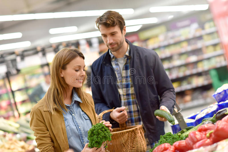 Couple at grocery store buying fresh vegetables royalty free stock photo