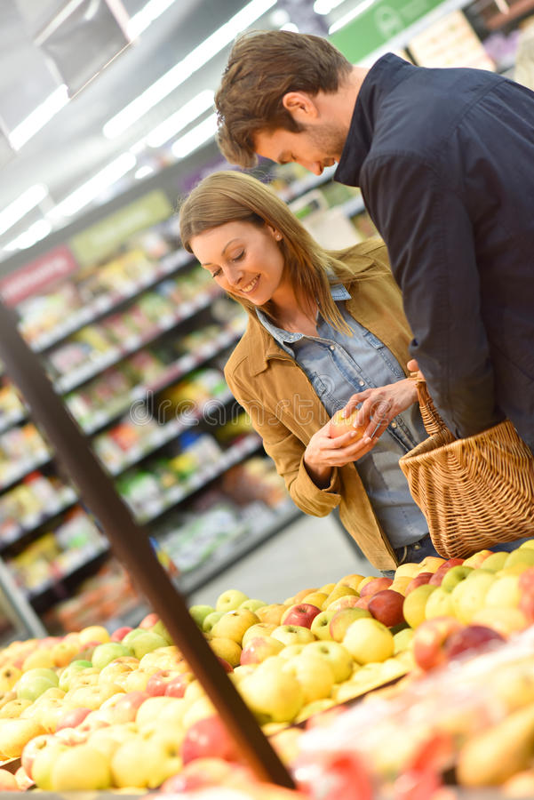 Couple at grocery store buying fruits stock images