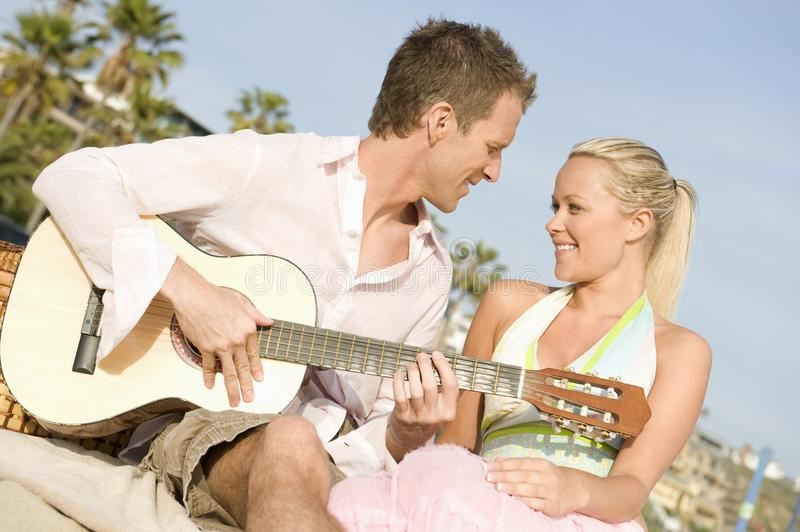 Couple With Guitar. Young romantic couple with guitar royalty free stock photo