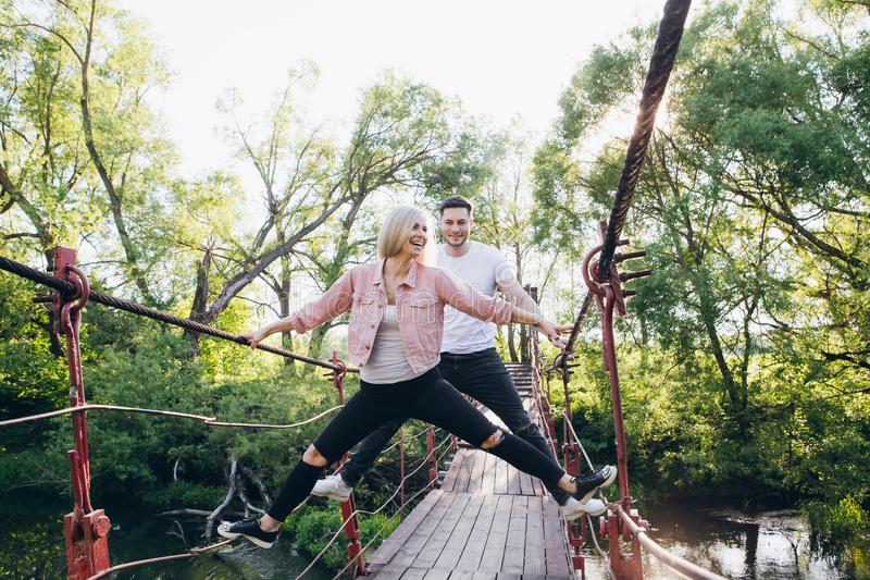 Couple guy and girl on the bridge over the river fooling around. Young couple guy and girl on the bridge over the river fooling around in the summer at sunset royalty free stock photo