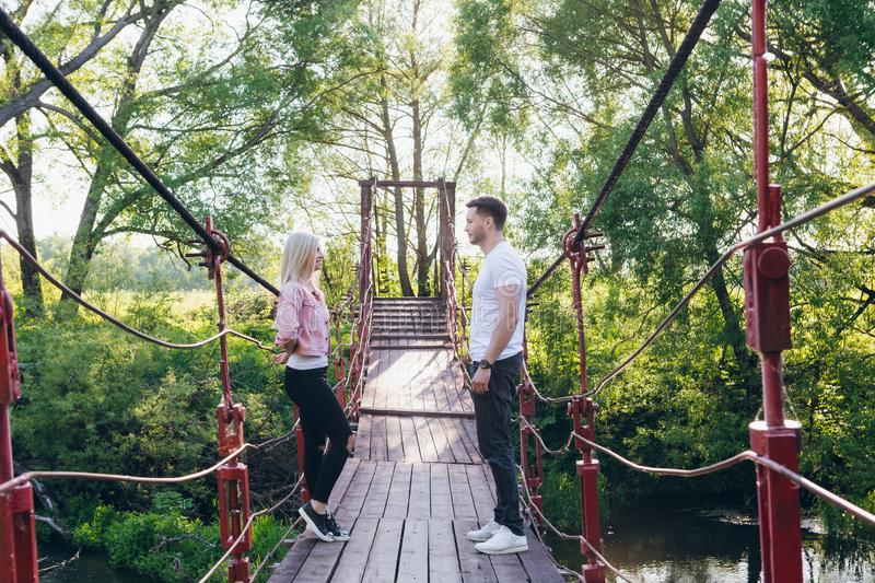 Couple guy and girl on the bridge over the river fooling around. Young couple guy and girl on the bridge over the river fooling around in the summer at sunset stock photos