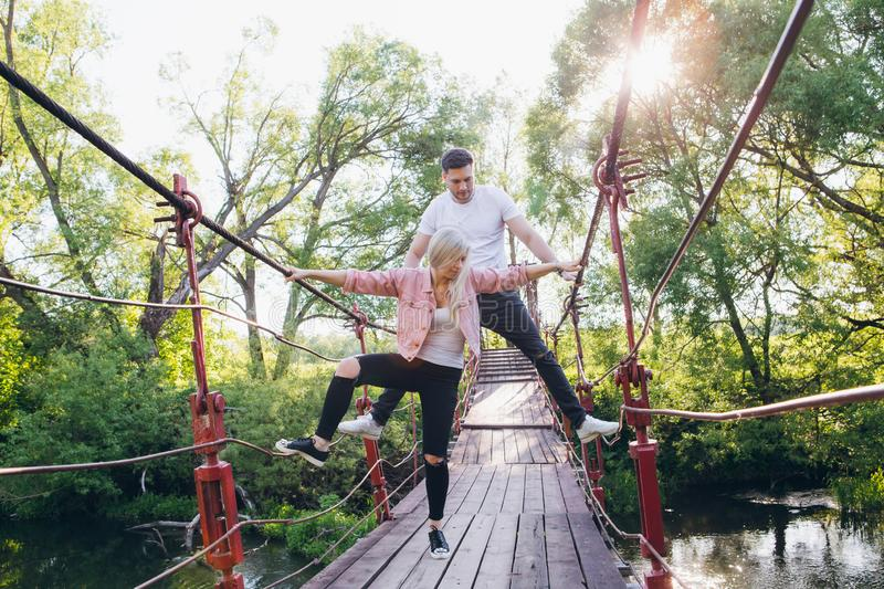Couple guy and girl on the bridge over the river fooling around. Young couple guy and girl on the bridge over the river fooling around in the summer at sunset stock photo