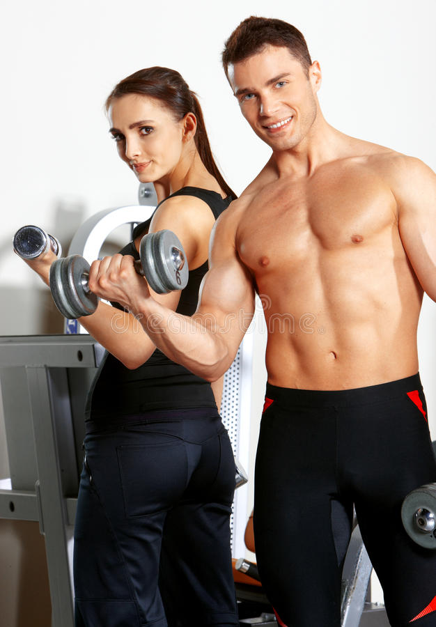 Couple at the gym. Sporty couple exercising at the fitness gym