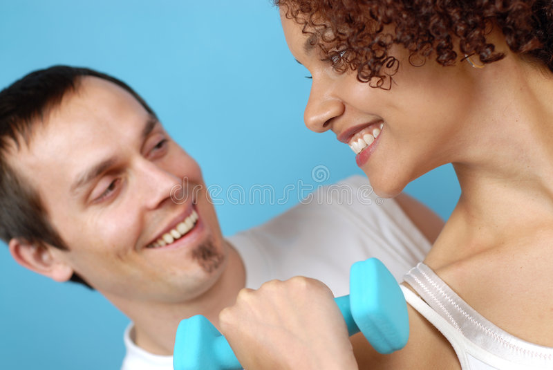 Couple at the gym. Healthy, loving couple working out together and having fun at it stock image