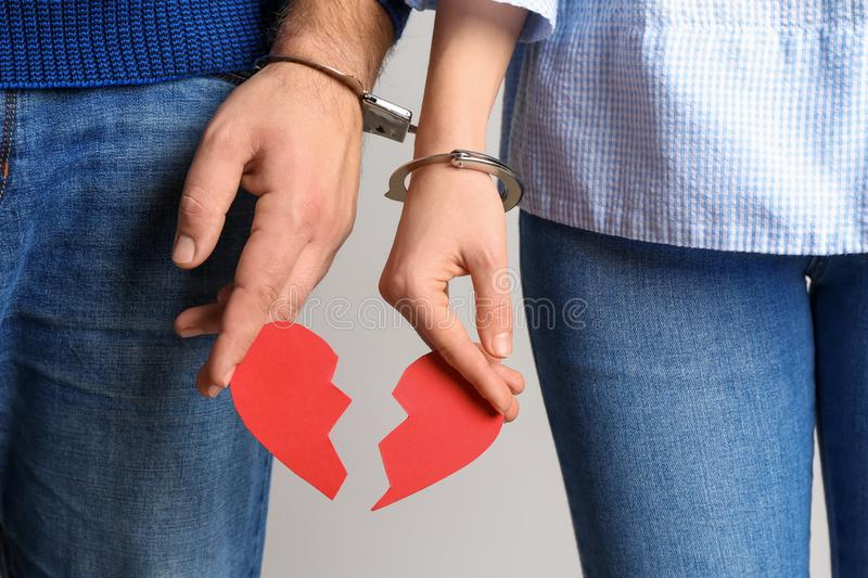 Couple with handcuffed together hands holding broken heart on light background. Concept of addiction stock images