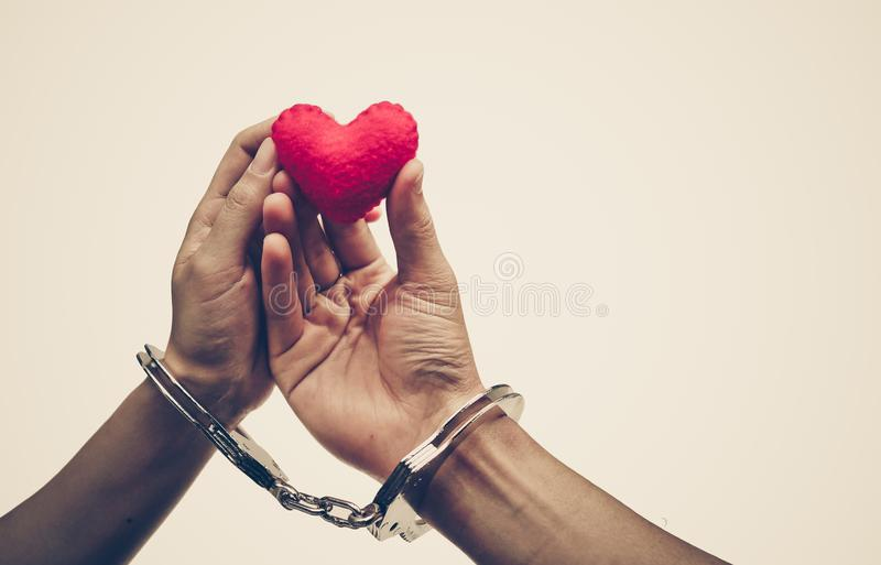 A couple` hands holding as a red heart together with hand cuffs stock photos