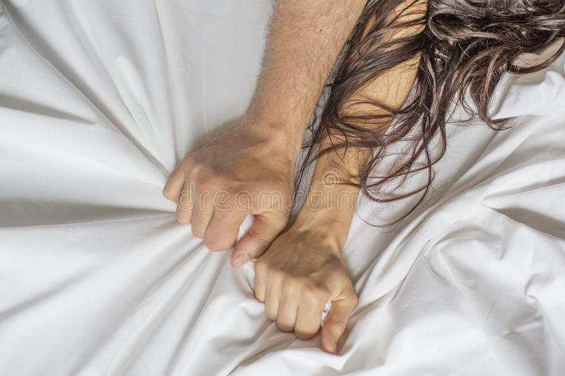 Couple hands pulling white sheets in ecstasy, orgasm. Concept of passion. Oorgasm. Erotic moments. Intimate concept. Sex. Couple. Bedroom. Hotel room. Spa royalty free stock photography
