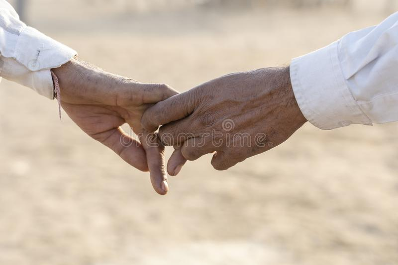Couple hands on the street during Pushkar Camel Mela. Pushkar, Rajasthan, India, close up. In India, it is normal to go to men royalty free stock photos
