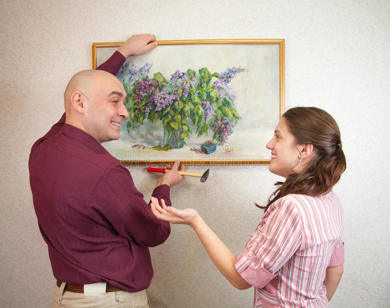 Download Couple Hanging Up An Art Picture On Their Wall Stock Image - Image: 13004765