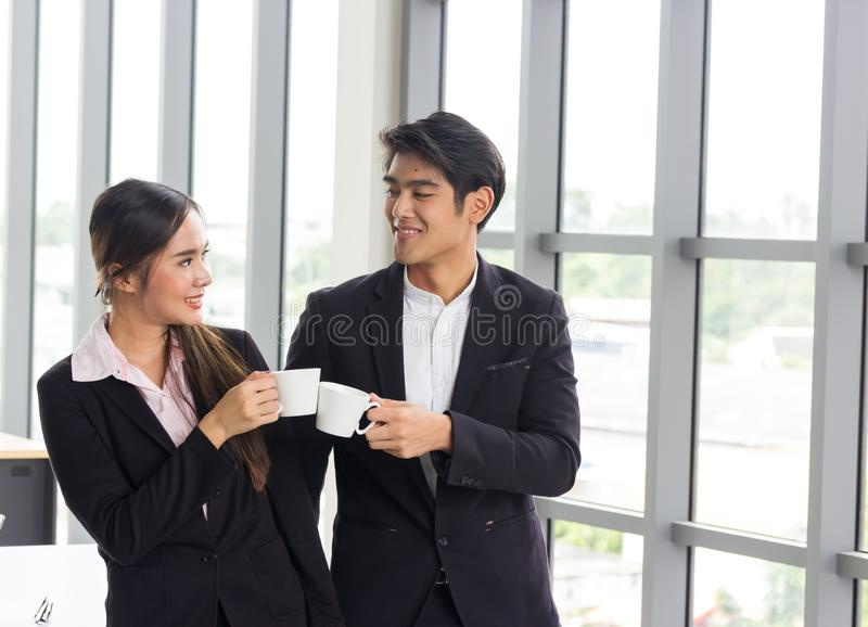 Couple of happy Asian colleagues talking while standing at the office window with cups of coffee.Concepts about teamwork royalty free stock images