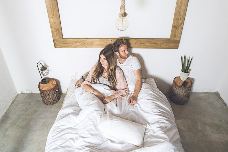 Couple of happy girl and guy smiling in bed at home stock photo