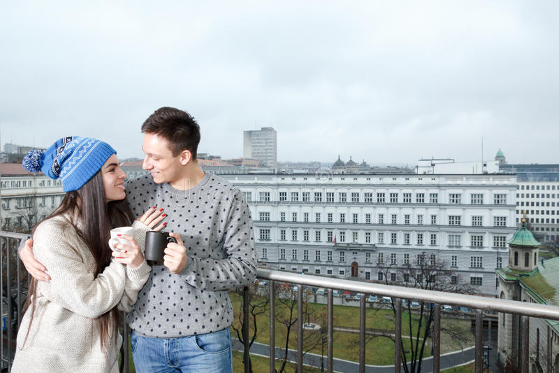 Couple happy in love hugging near railing with cups of tea or co. Ffee. Man and women drinking hot beverage outdoor on balcony in winter or autumn in cardigan or stock images
