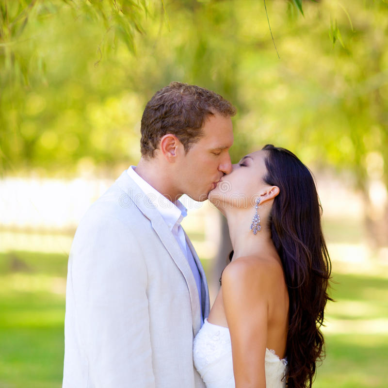 Couple happy in love kissing in the park stock images