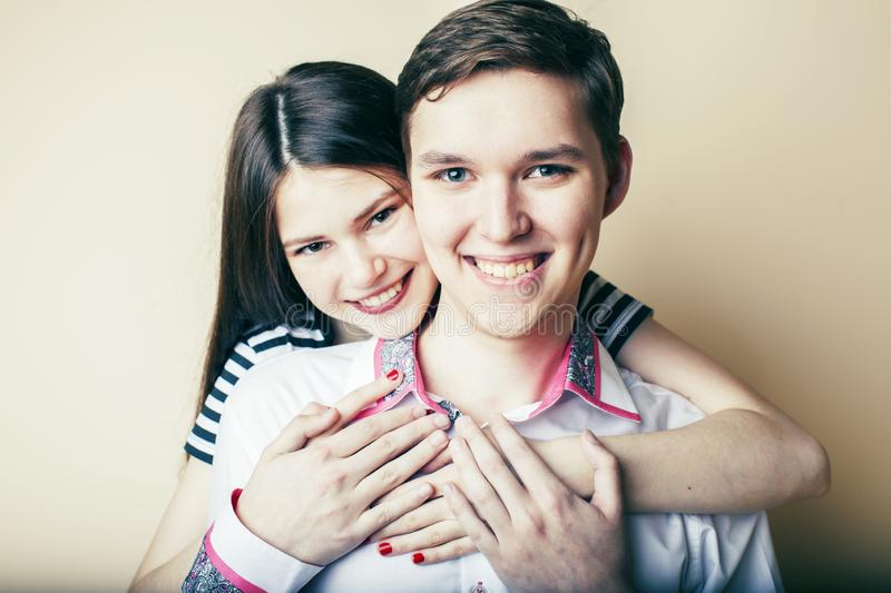 Couple of happy smiling teenagers students, warm colors having a kiss, lifestyle people concept, boy and girl together stock images