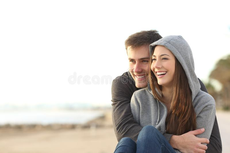 Couple of happy teens looking away on the beach. Couple of happy teens looking away and laughing on the beach stock photo