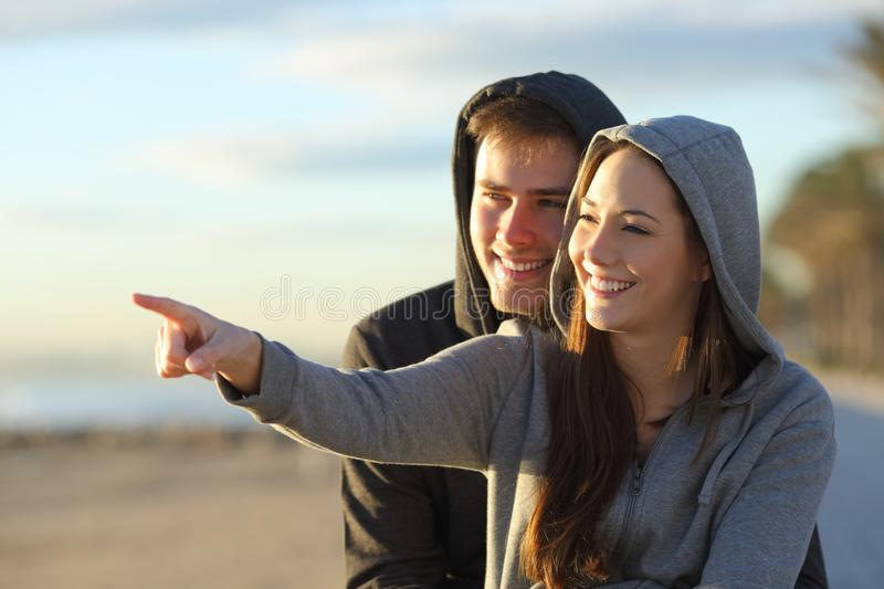 Couple of happy teens pointing at horizon royalty free stock image