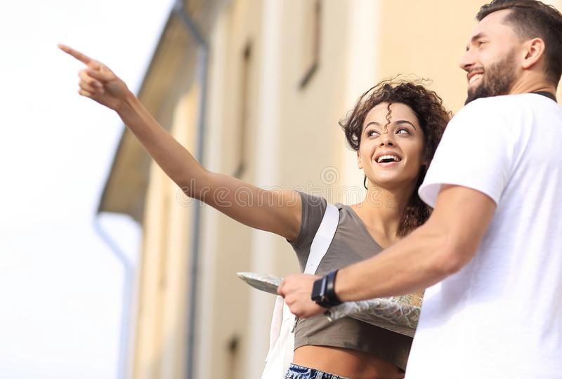 Happy man showing something to woman outside building royalty free stock image