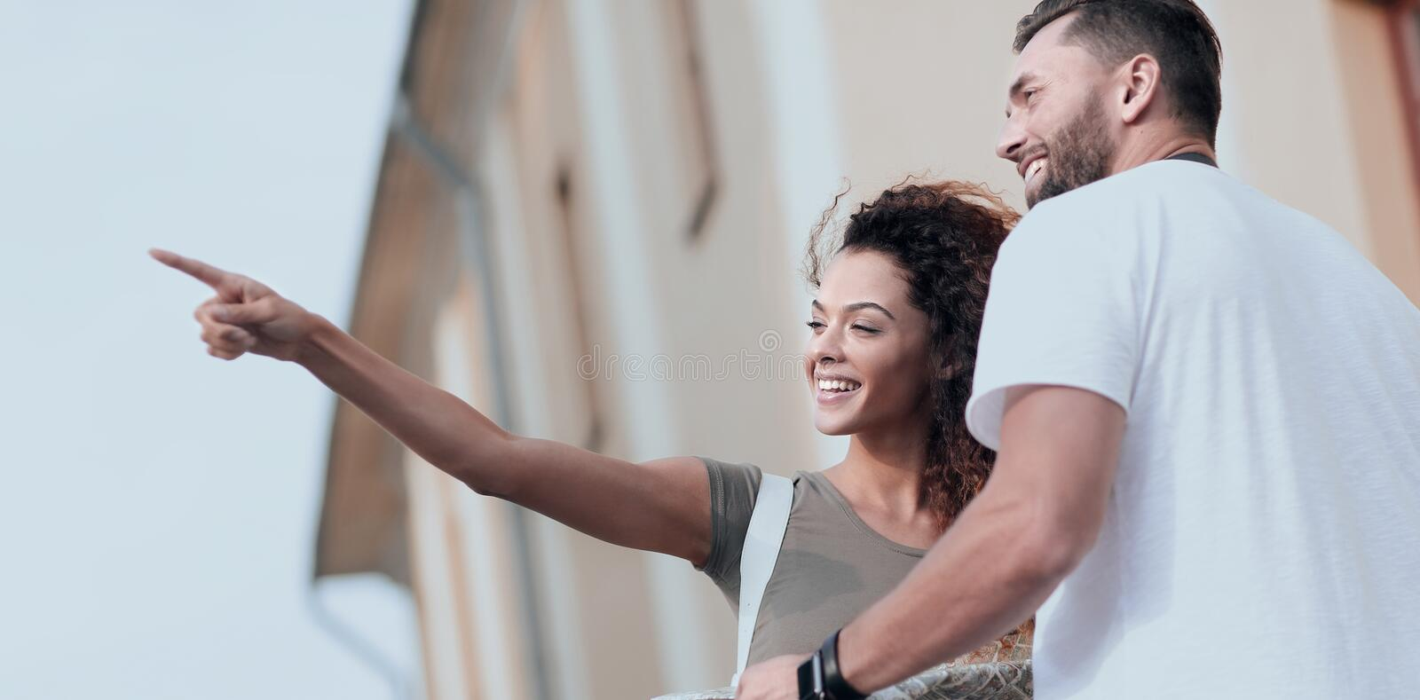 Happy man showing something to woman outside building royalty free stock photo