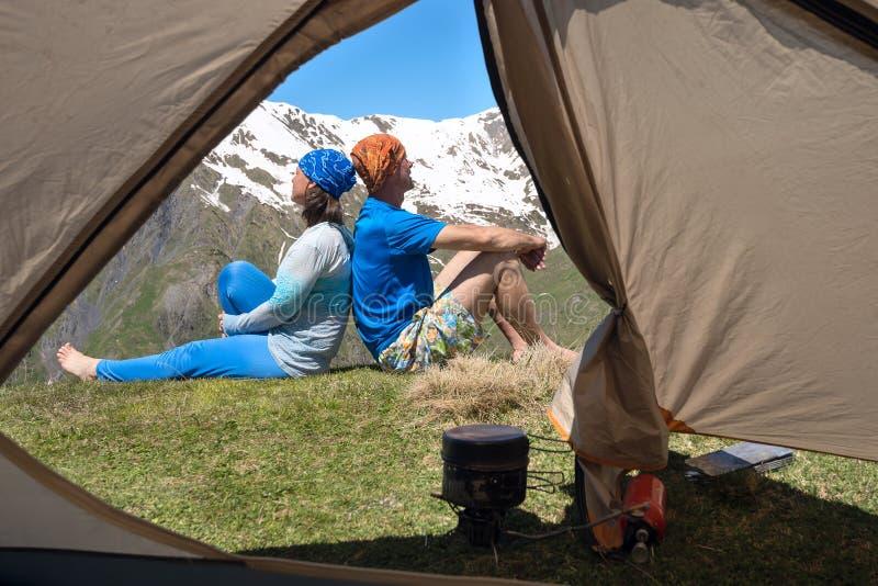Couple of happy travelers a sitting on a edge precipice, enjoyin royalty free stock photos