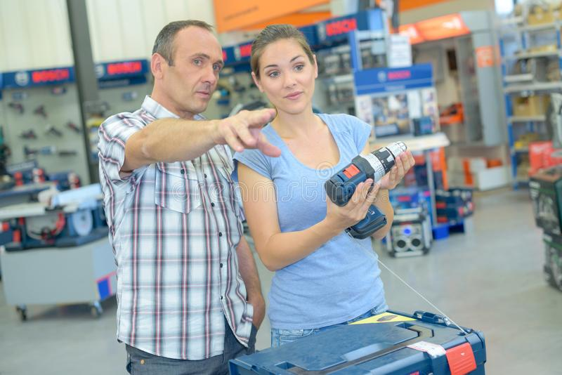 Couple in hardware shop man pointing. Couple in hardware shop men pointing power stock photos