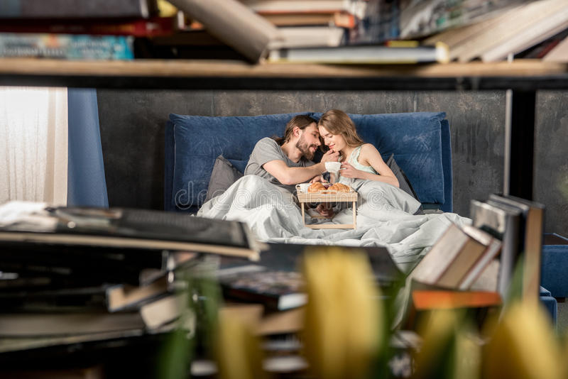 Couple has breakfast in bed royalty free stock photography