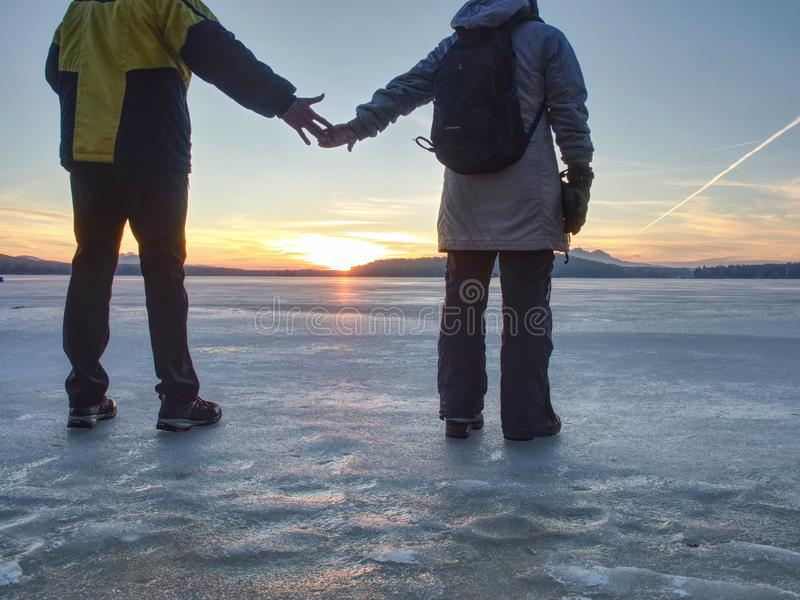 Couple has fun during winter walk on ice of frozen lake. Evening hike at beach of pond. Warm clothes pair with high warm boots, two, traveler, sunrise, smile royalty free stock images