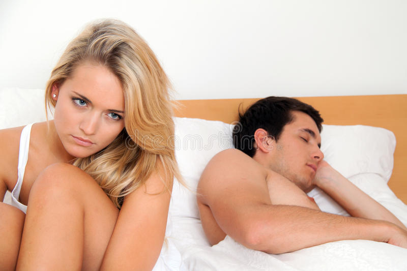 Couple has problems and crisis. A young couple in bed having problems and crisis. Divorce and separation stock images