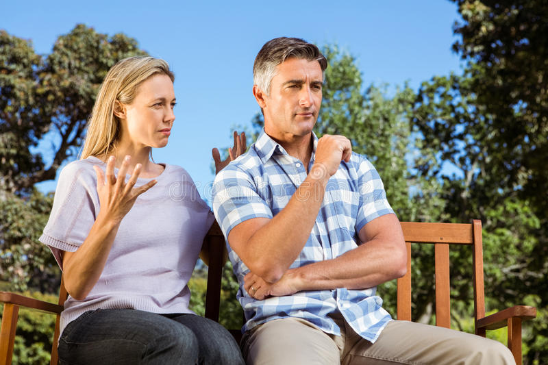 Couple having an argument on park bench. On a sunny day stock image
